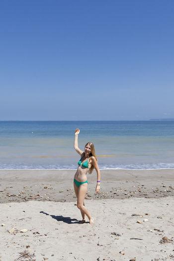 Happy woman in bikini standing on shore at beach