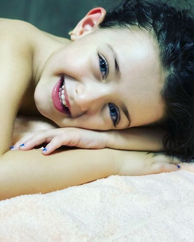 Close-up portrait of cute girl on bed