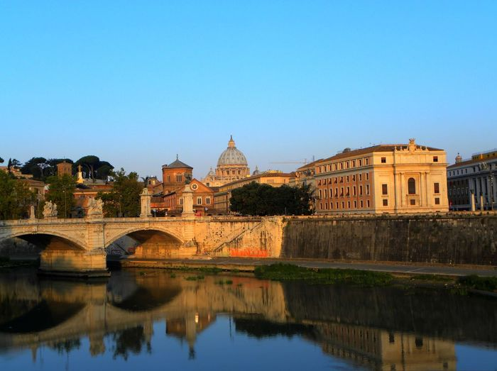 Bridge over river by st peter basilica against clear blue sky in city