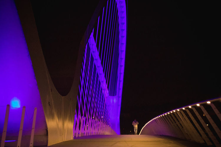 Illuminated Night Architecture Built Structure Real People Lifestyles Lighting Equipment One Person Sky Incidental People Motion Building Exterior Leisure Activity City Men Standing Bridge Women Unrecognizable Person Purple Outdoors Modern Nightlife Colors Silhouette Lines The Architect - 2019 EyeEm Awards