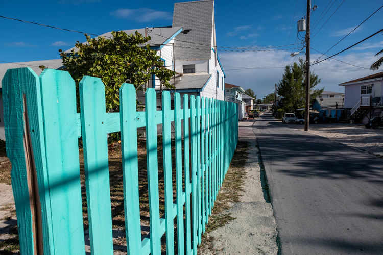 Green Wooden Fence Plant Nature Built Structure Sky Architecture Sunlight Fence Building Exterior Tree Day Barrier Boundary No People Blue Road City Building Outdoors Shadow Street Turquoise
