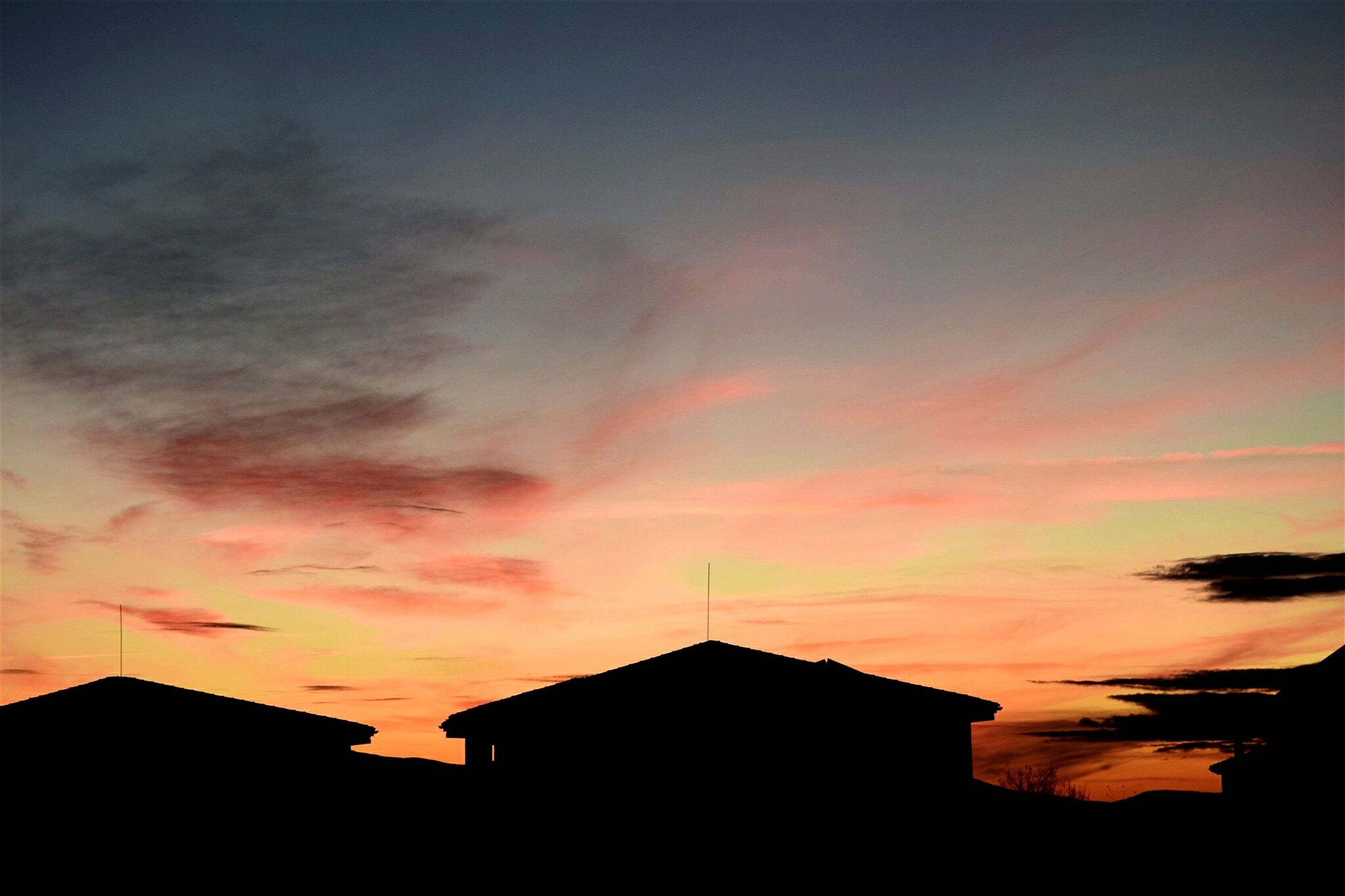 building exterior, architecture, sunset, built structure, sky, silhouette, orange color, low angle view, city, cloud - sky, residential structure, building, residential building, house, cloud, outdoors, no people, high section, dusk, dramatic sky