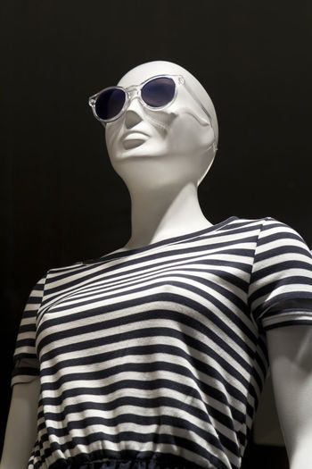 Low angle view of mannequin against black background