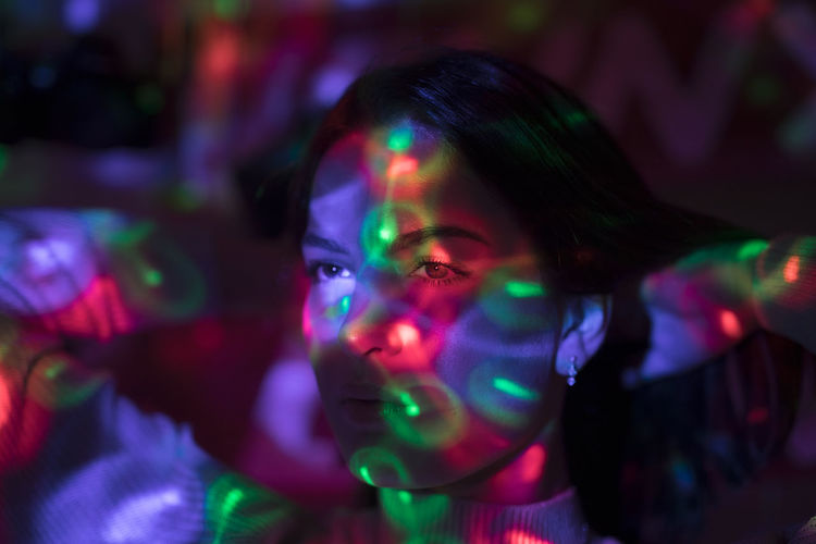 Close-up of colorful lights falling on woman face