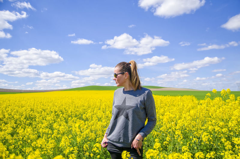 Rear view of young woman standing by yellow flowers on field