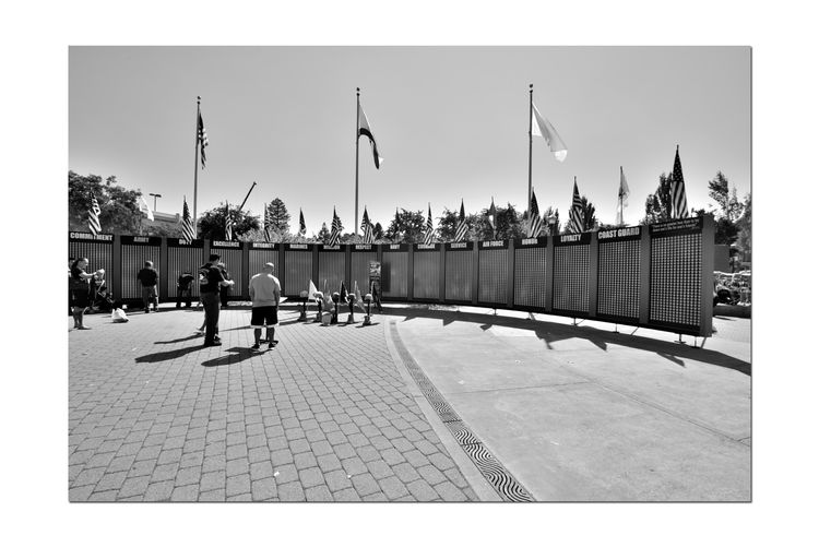 Gold Stars Tribute Wall 3 A Traveling Memorial Honoring The Fallen & Their Families U.S. Military Gulf, Iraq & Afghanistan Wars Promote Public Awareness Stars: Names Of The Fallen Fallen Soldiers The Ultimate Sacrifice Bnw_friday_eyeemchallenge Bnw_memorials Black & White Black & White Photography Black And White Black And White Collection  Memorial People Commemorate Helmet, Arms & Boots Flags Courtyard  Remembrance Text Branches Of Service Gold Stars Tribute Wall City Sky Western Script Information