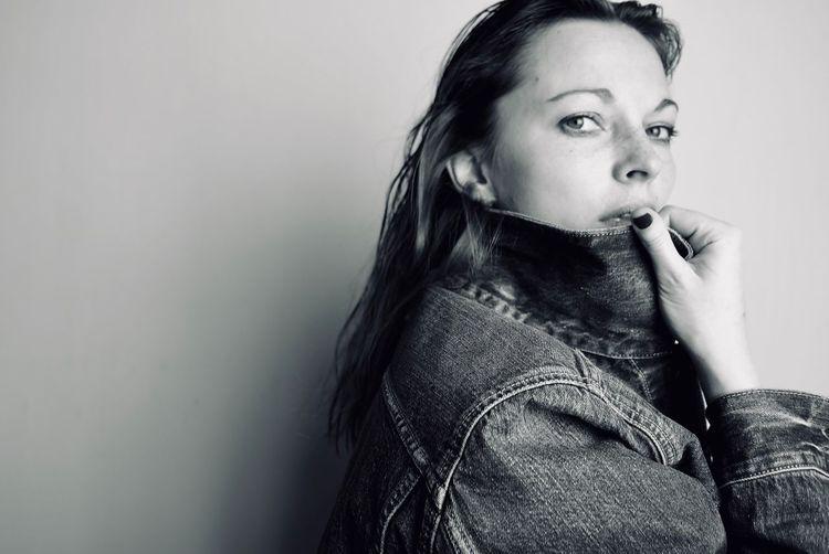 Portrait of woman wearing denim jacket against wall