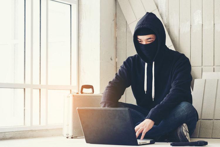 Burglar using laptop with gun on floor