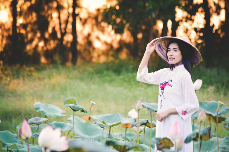 Beautiful woman wearing conical hat standing amidst lotus buds