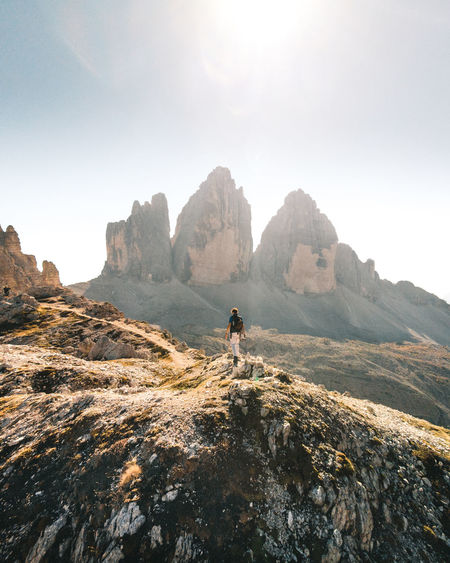 Man on rocks by mountains against sky