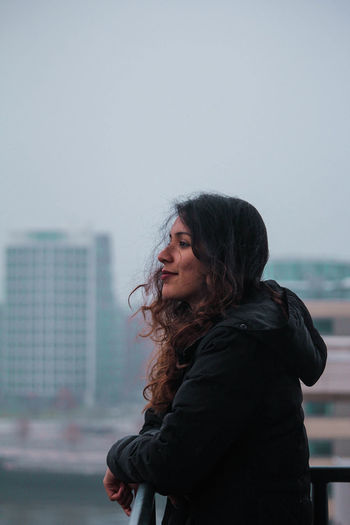 Side view of smiling young woman standing in city against sky