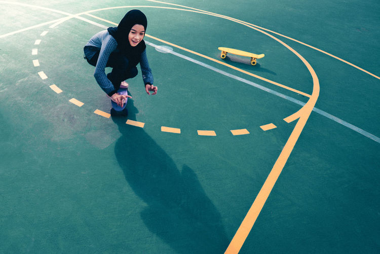 High Angle View Of Teenage Girl Skateboarding At Basketball Court