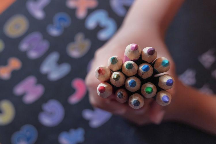 Child boy hand holding color pencils