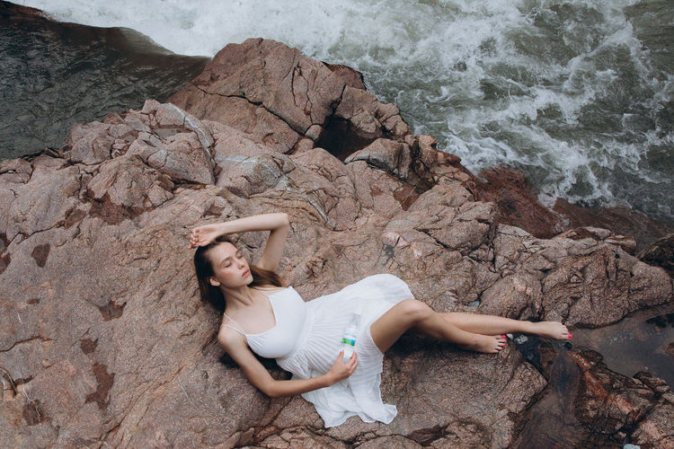 High angle view of woman on rock at beach