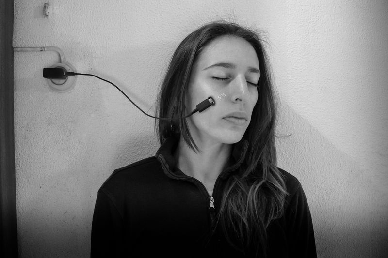 Eyes closed young woman with mobile charger on cheek against wall