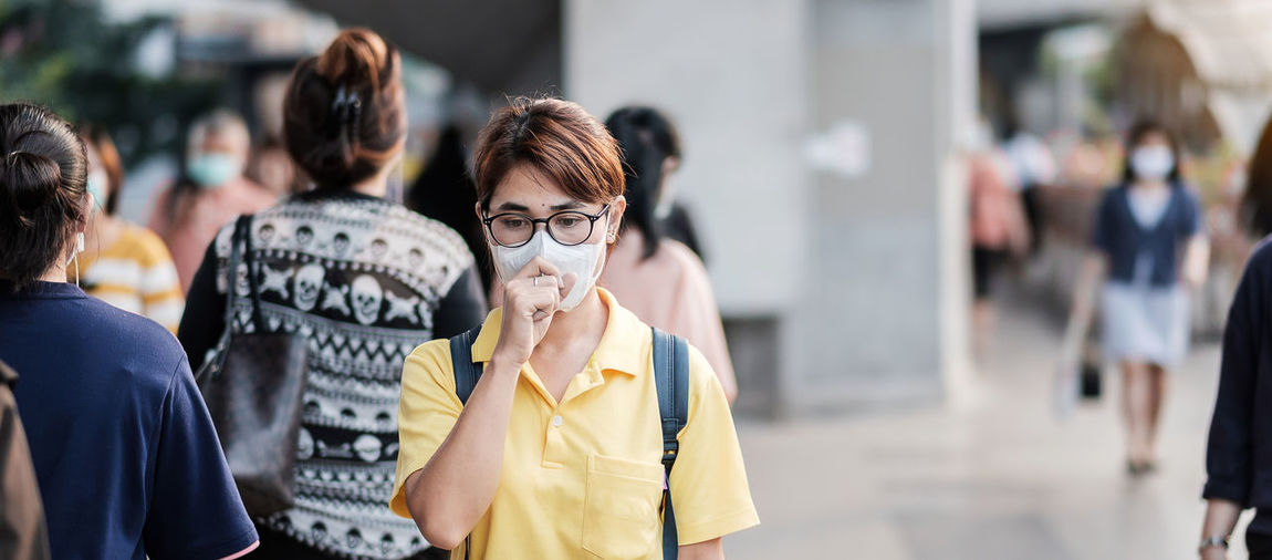 Woman with pollution mask coughing in city