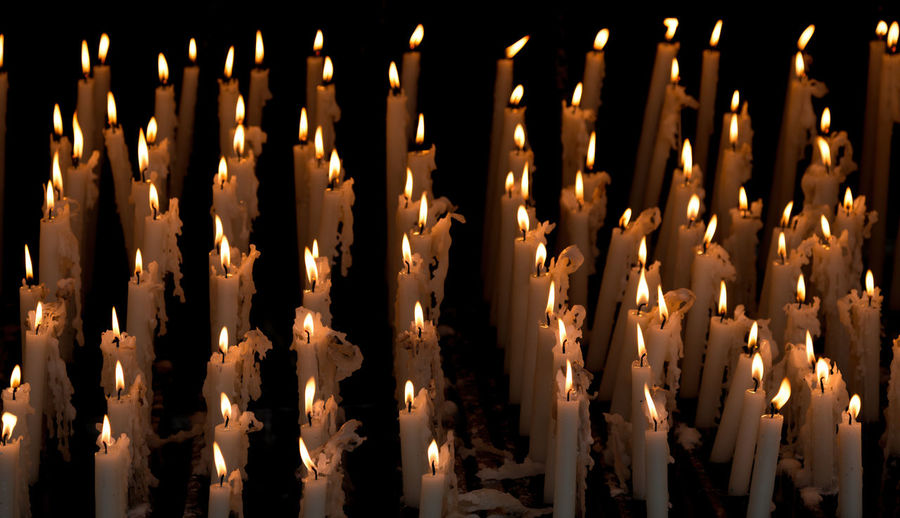 Close-up of illuminated candles against black background