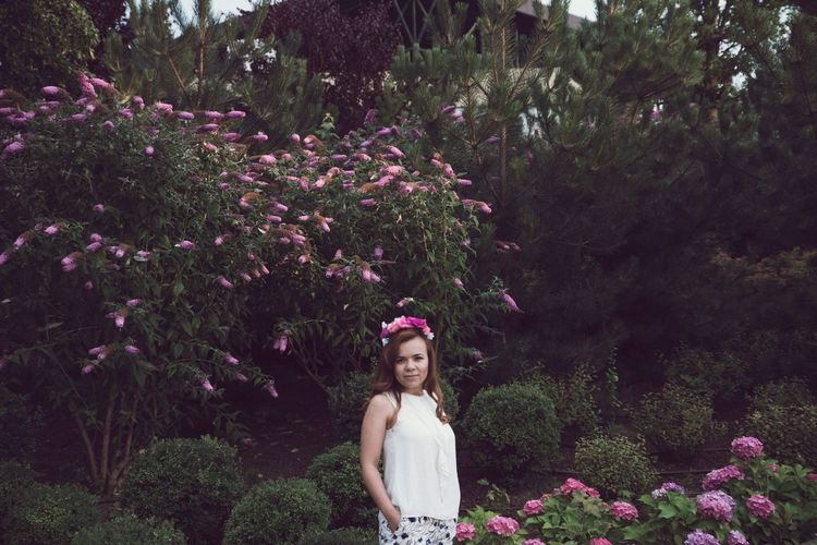Portrait of young woman standing amidst plants at park