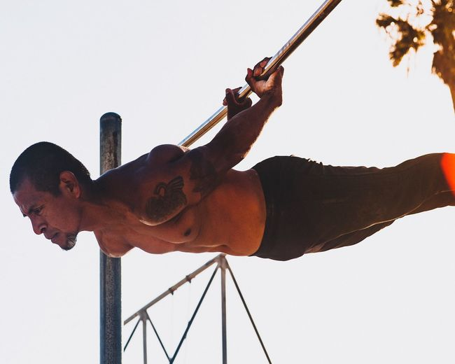 Low angle view of shirtless mature man exercising on pole against clear sky