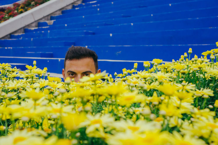 Portrait of man with yellow flowering plants