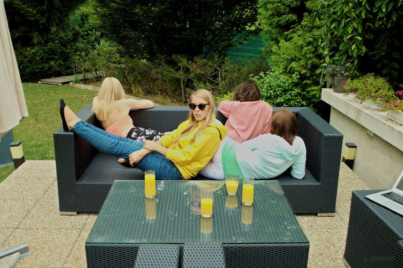 Sitting Togetherness Women Group Of People Casual Clothing Sofa People Summer Outdoors Front Or Back Yard Lying Down Adult Reflection Glass - Material Glass Juice Orange Juice  Yellow Hanging Out Mood Girls Girl Portrait Legs Leisure Activity