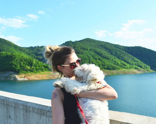 Young Woman Kissing Dog While Standing Against River