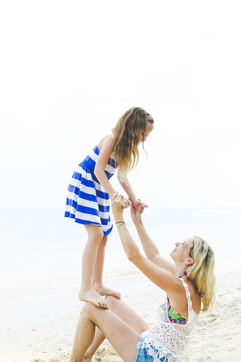 Girl Standing On Knees Of Mother At Beach