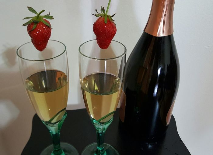 Pair of wineglasses on table garnished with strawberries