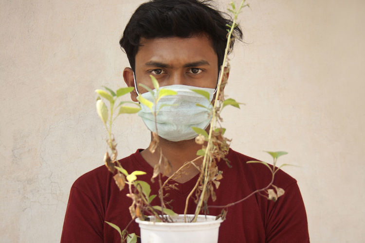 Portrait of young man holding plant against wall