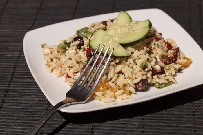 Greek orzo salad with cucumbers, sundried tomatoes, olives, onions, peppers and feta cheese on a white plate with a silver fork. Cucumbers Fetta Cheese Food Freshness Greek Food Greek Orzo Health Healthy Eating Lunch No People Olives Orzo Peppers Ready-to-eat Salad Sundried Tomato