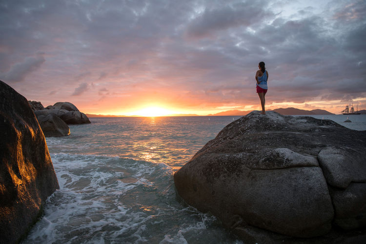 Rear view of man standing on rock against sea during sunset