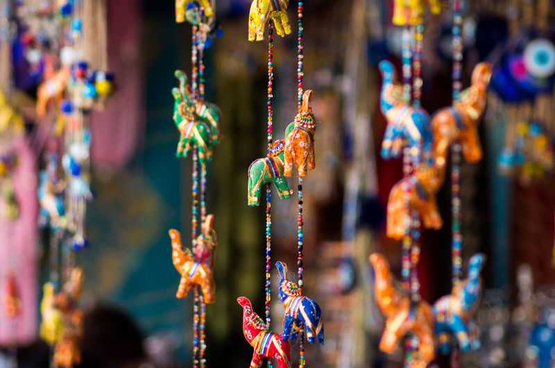 Colorful Figurines Hanging At Market For Sale