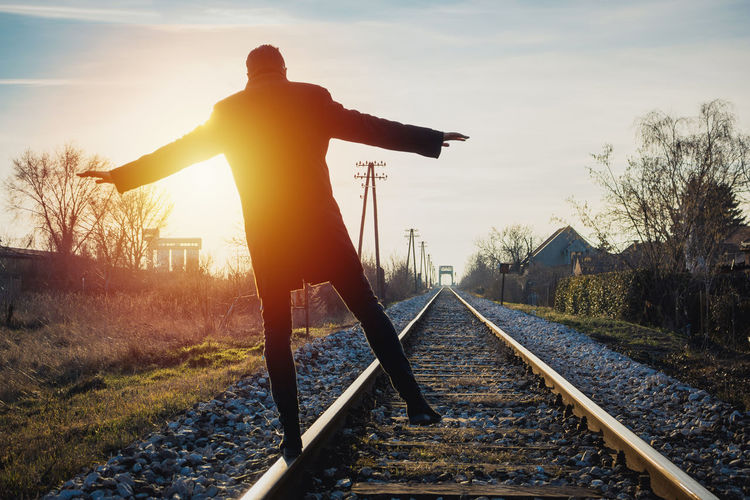 Silhouette man standing by railroad tracks against sky during sunset