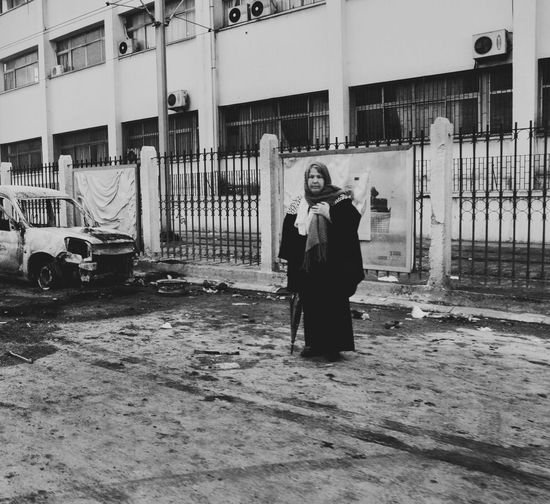 Full length of woman standing against car
