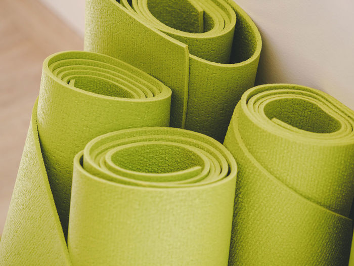 Close-up of green rolled exercise mats