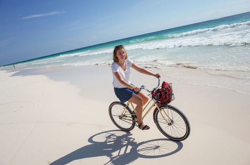Woman riding bicycle on beach
