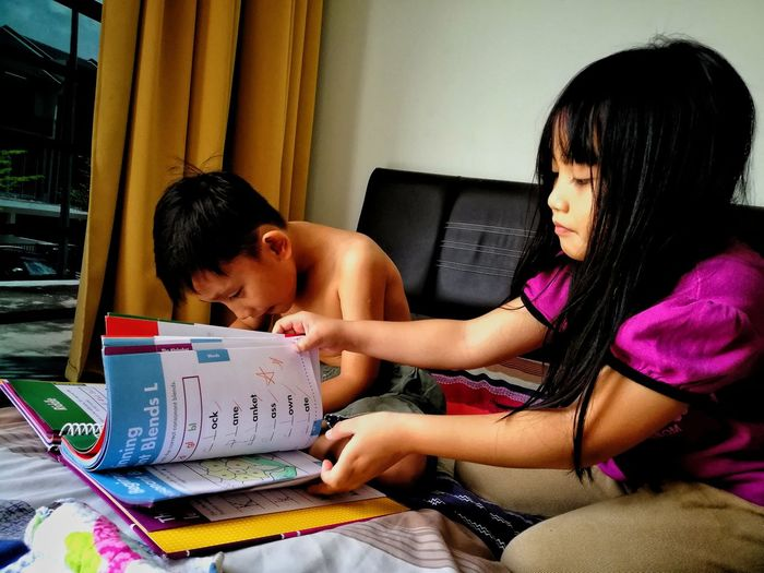 Siblings studying on bed at home