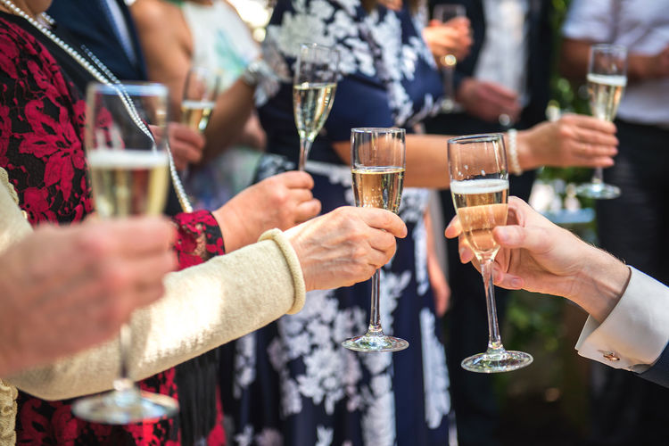 Cropped Hands Of Friends Toasting Champagne Flutes In Party