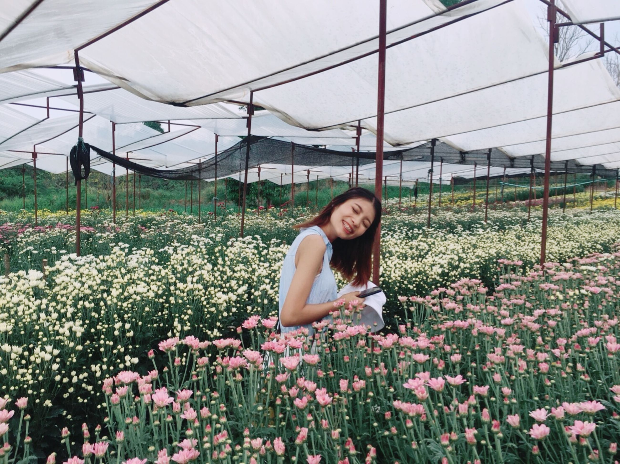 plant, one person, young adult, flower, growth, real people, flowering plant, greenhouse, young women, nature, beauty in nature, portrait, looking at camera, women, lifestyles, smiling, day, casual clothing, freshness, beautiful woman, outdoors, hairstyle, gardening