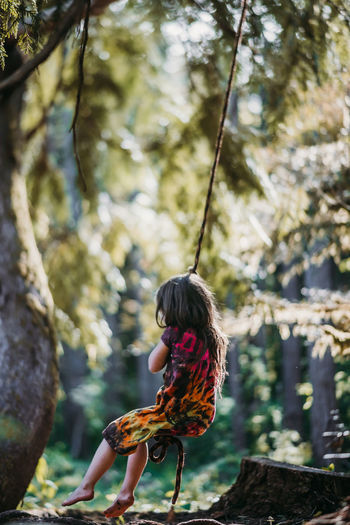 Woman sitting on rope in forest