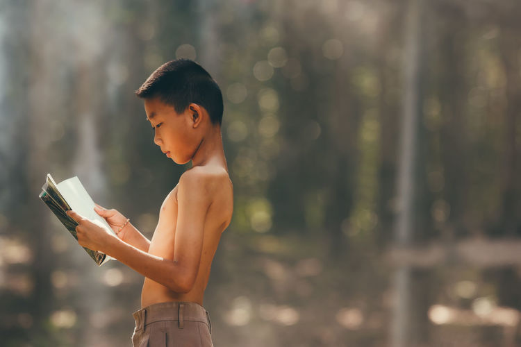 Side view of shirtless boy reading book on field