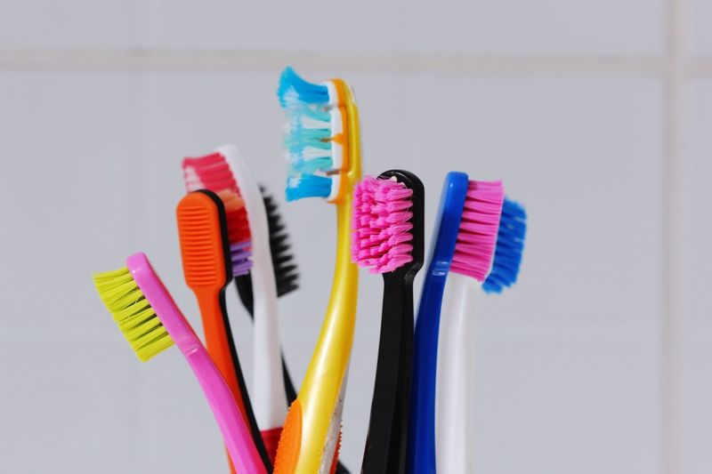 Close-up of multi colored toothbrushes in bathroom