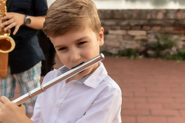 Small musician playing flute outdoors.