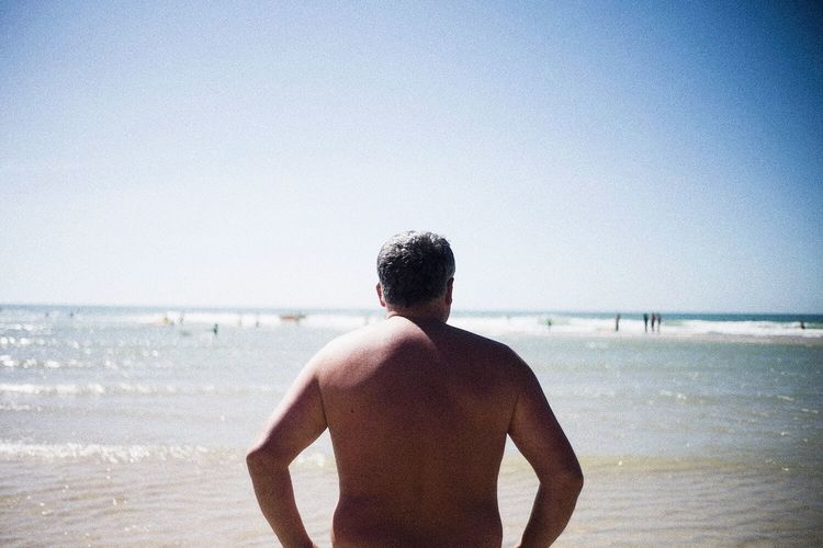 Rear view of man standing in front of sea
