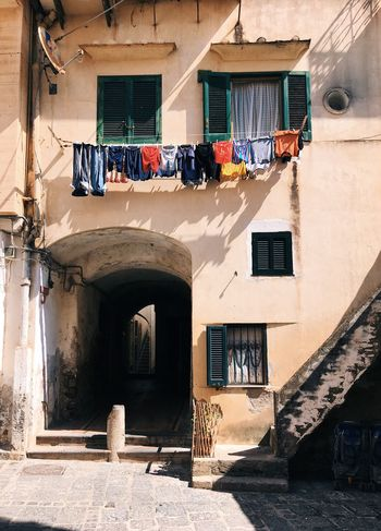 colorful clothes are drying in the streets of Italy Italy Windows Vintage Building Drying Multicolors  Yellow Color Red Color Clothes Colorful Clothes Colorful Amalfi Coast Architecture Built Structure Building Exterior Building Sunlight Day Wall - Building Feature Entrance Wall