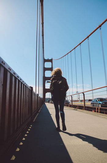 Rear view of woman walking on bridge against blue sky