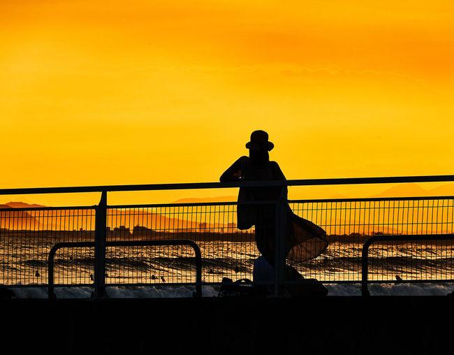 Silhouette women standing on bridge against sky during sunset