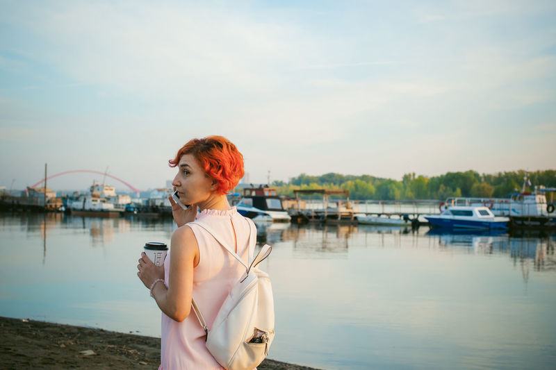 Mid adult woman talking on mobile phone while standing by river against sky during sunset