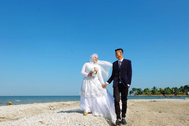 Couple holding umbrella while standing on shore against blue sky