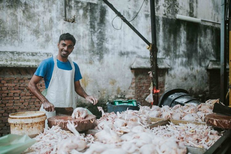Portrait of happy butcher cutting meat at market stall